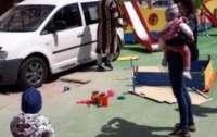Под Киевом мужчина в халате припарковал авто на детской площадке
