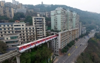 Нам такое и не снилось. В Китае поезд идет через 19-этажный жилой дом (видео)