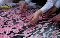 В Китае ребенок порвал банкноты на $10000
